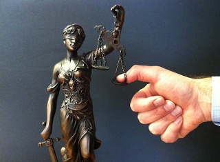 Thumb on Scales of Justice